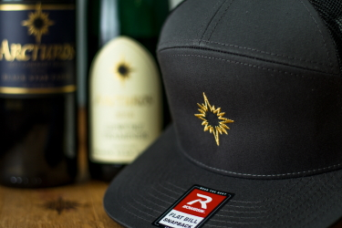 Photo of a Black Star Farms Flat-Bill Hat and a bottle of Cabernet Franc and Gewurztraminer
