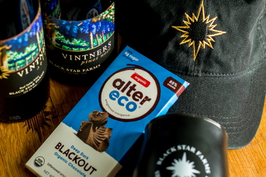 Photo of Black Star Farms Vintners Select, dark chocolate, a logo hat, and wine tumbler.