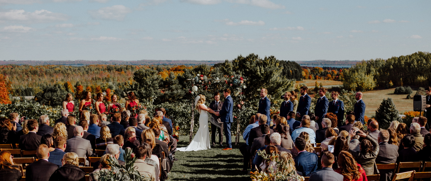 October wedding ceremony with couple and attendees atop our vineyard with beautiful fall colors.
