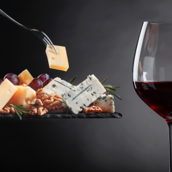 Glass of red wine with a cheese board. including a variety of cheeses and nuts.