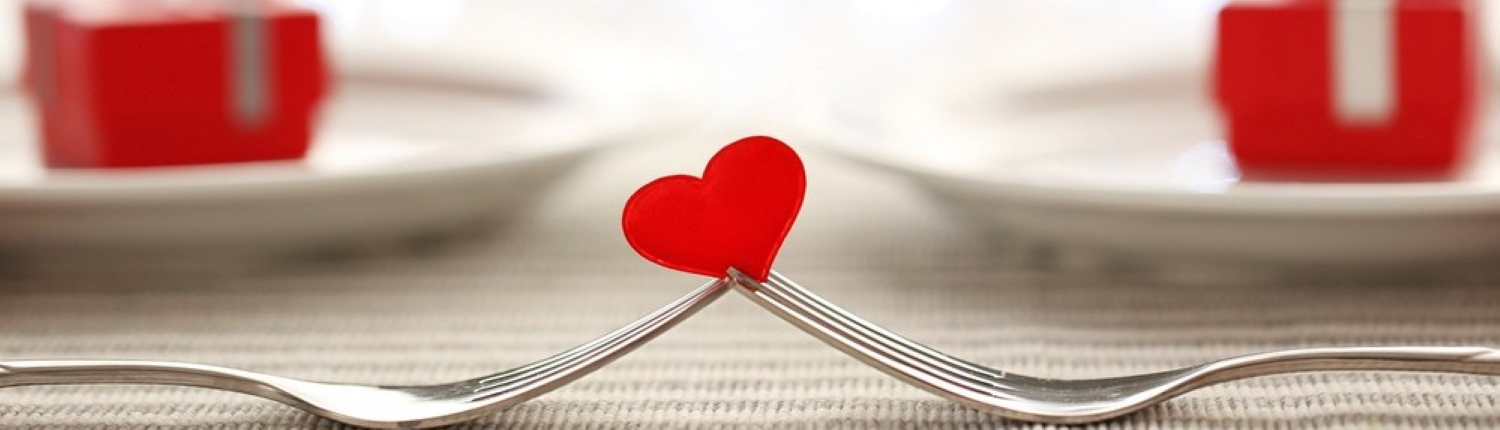 Image of two forks balancing a red heart.
