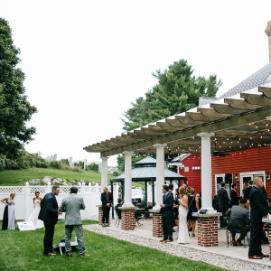 Wedding guests enjoying the covered patio and lawn off the back of the Inn at Black Star Farms.