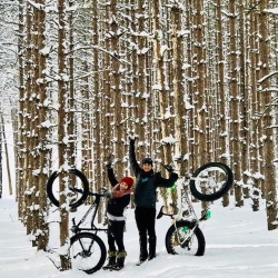 A couple with fat tire bikes in the snow.