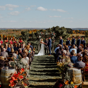 Fall wedding ceremony with bride, groom, officiant, and attendees atop our vineyard.