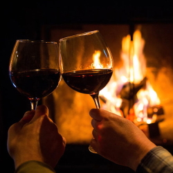 Couple enjoying wine in front of a fireplace at the Inn at Black Star Farms.