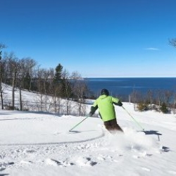 Man downhill skiing at the Homestead Resort overlooking Lake Michigan.