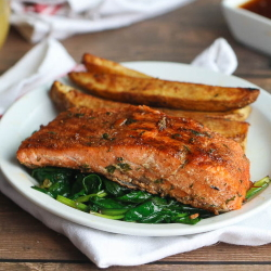 Example of salmon with Jamaican jerk seasoning over spinach with roasted potato wedges.
