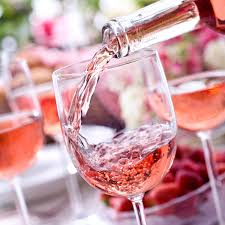 Image of rose wine being poured into a glass with other glasses of rose in the background.