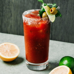 Bloody Mary cocktail with lime and olive garnish.