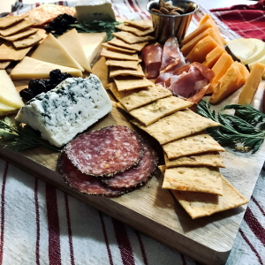 Charcuterie board with meat, cheese, and Black Star Farms house-made crackers.