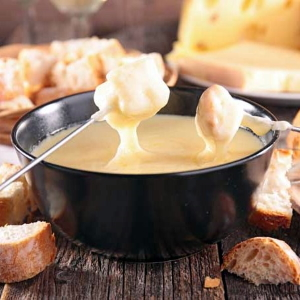 Dipping bread into cheese fondue, one of the pairings suggested in this blog post.