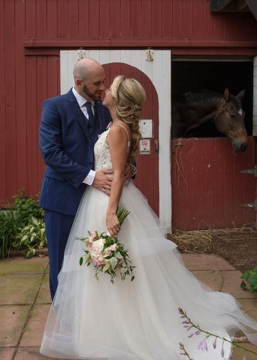 Bride and groom with a horse in a barn at the stables at Black Star Farms.