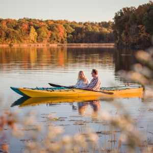 Couple kayaking during the fall as part of our Outdoor Adventure Package.