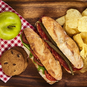 Example of a picnic lunch with sandwiches, chips, an apple and cookies.