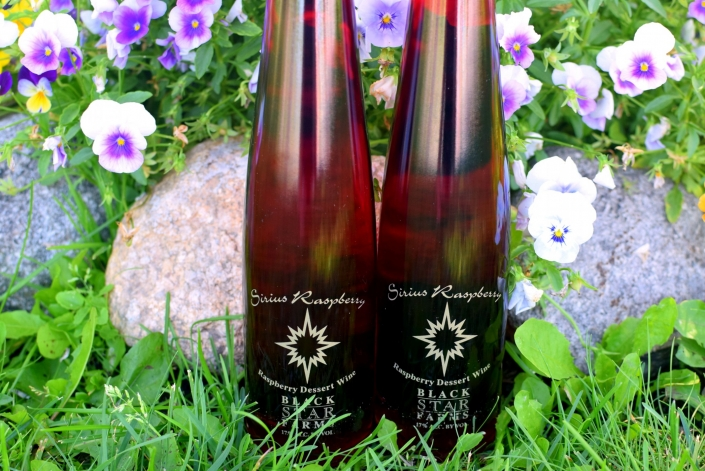 Two bottles of Sirius Raspberry Dessert Wine placed in front of colorful pansies.