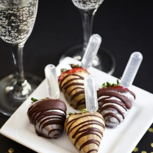 Chocolate covered strawberries with glasses of sparkling wine.
