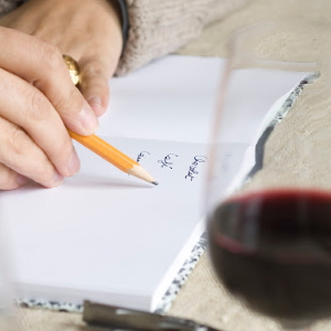 Person taking wine tasting notes.