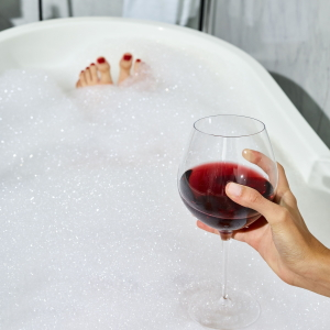 Soaking in a bubble bath with a glass of red wine.