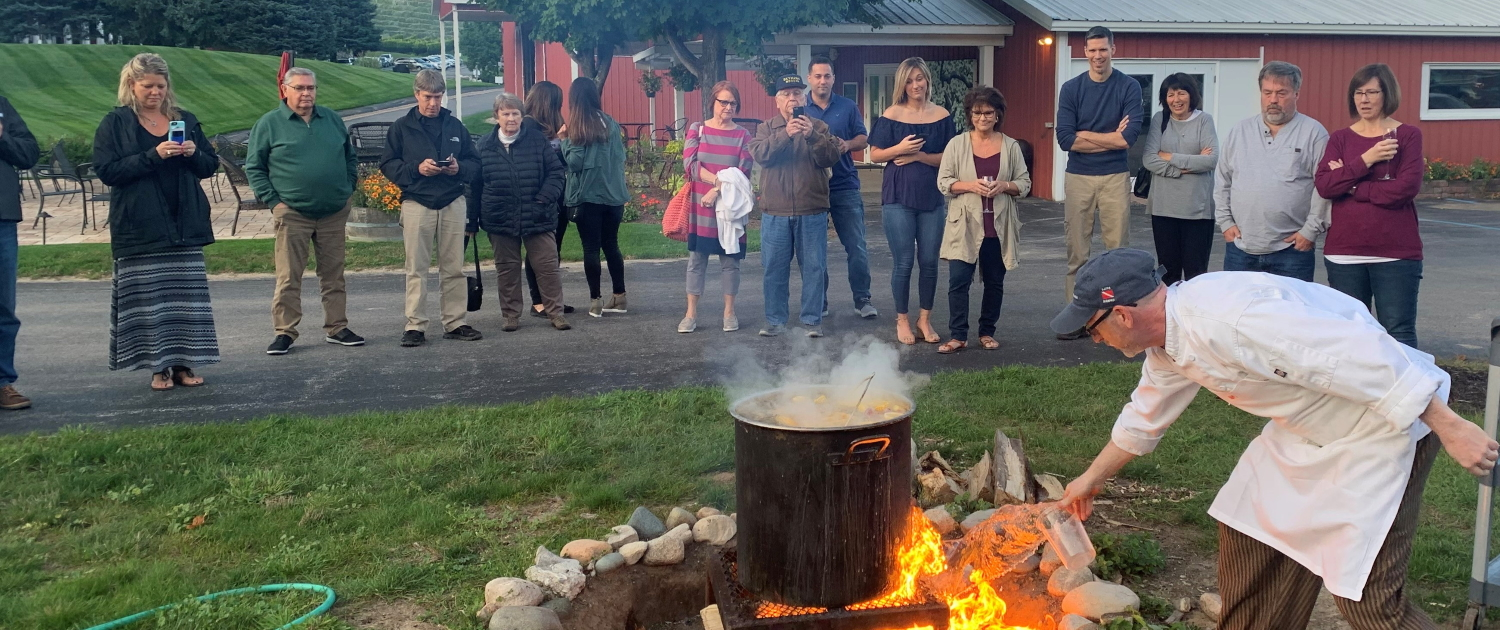 Lighting the fire for the boil over at the Great Lakes Fish Boil at the Hearth & Vine Cafe.
