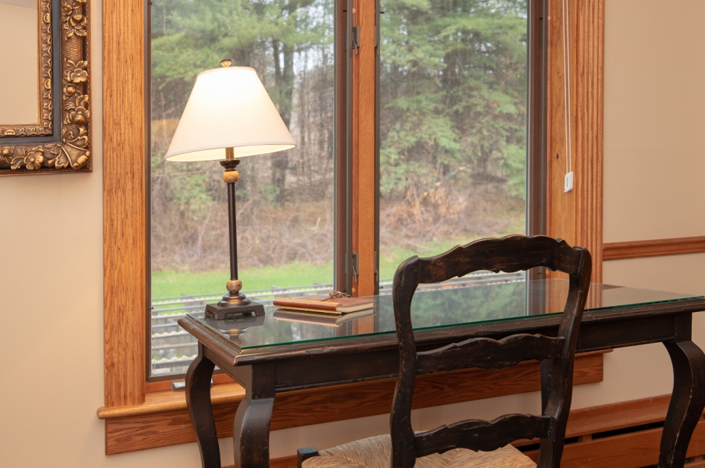Writing desk with windows overlooking the forest.