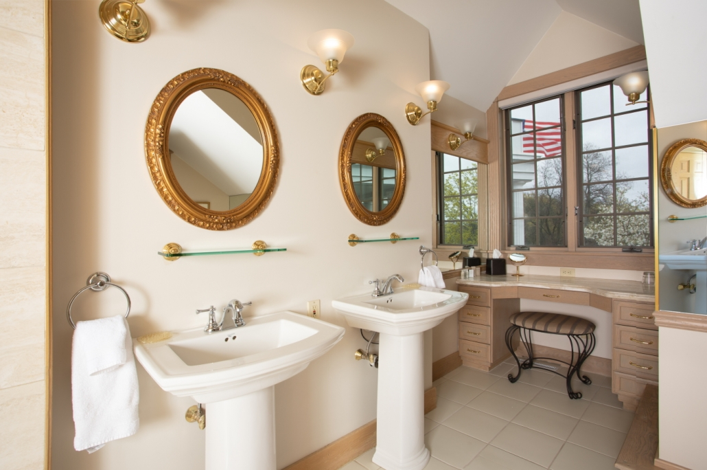 Bathroom with dual pedestal sinks and vanity in Diadem suite.
