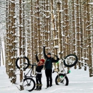 A couple with fat bikes in the snow.