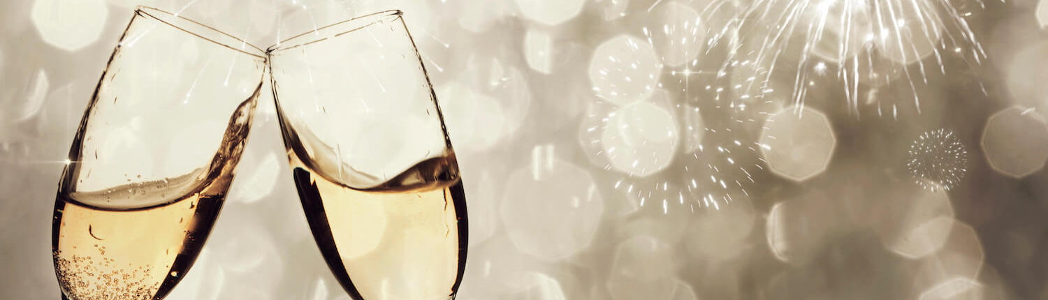 Two sparkling wine flutes clinking.