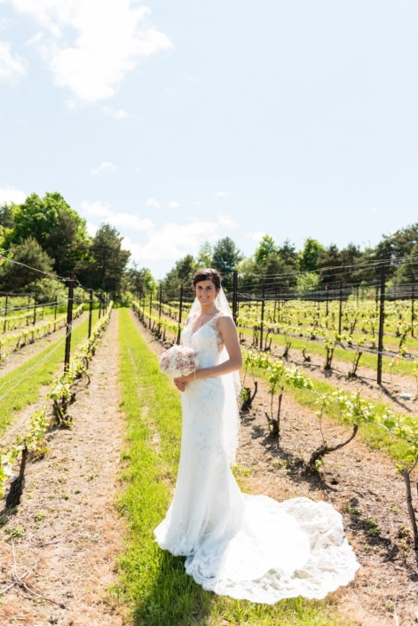 Bride standing in the vineyard during early summer.