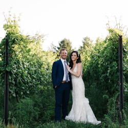 Bride and Groom standing between vineyard rows.