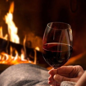 Women lounging by the fireplace with red wine.