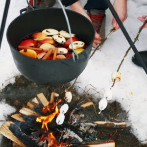 Mulled wine in a pot heating over a bonfire.