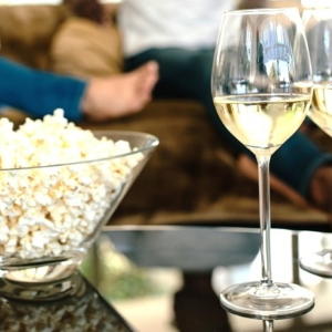 Bowl of popcorn with white wine.