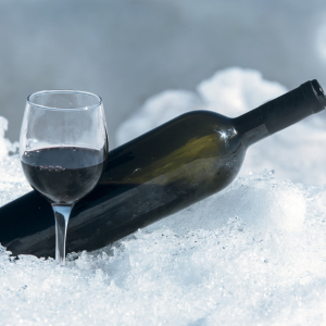 Glass and bottle of red wine in the snow.