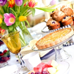 Brunch items on a table with flowers.