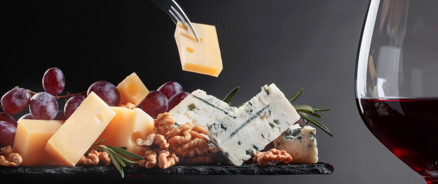 Cheese board with fruit and nuts and a glass of red wine.