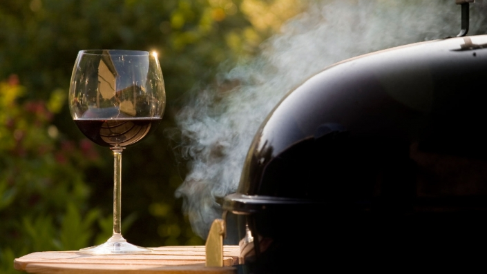 Image of a glass of wine next to a smoking grill.