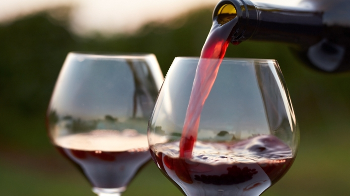 Pouring red wine into glasses.