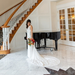 Bride standing near staircase and grand piano.